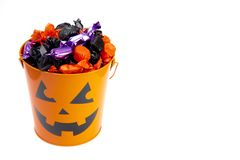 Pumpkin Bucket Filled with Various Wrapped Candies. On a White Background royalty free stock image