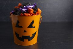 Pumpkin Bucket Filled with Various Wrapped Candies. On a White Background royalty free stock images