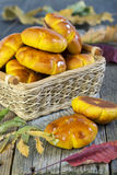 Pumpkin buns in a wicker basket. Basket with buns and autumn leaves on an old table Royalty Free Stock Photo