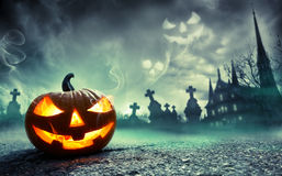 Pumpkin Burning In A Graveyard With Ghost. Nightmare Stock Photo
