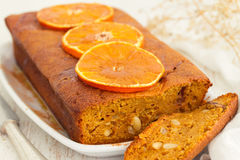 Pumpkin cake with orange on white dish on wooden background Stock Images