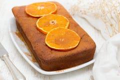 Pumpkin cake with orange on white dish on wooden background Stock Photo