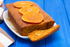 Pumpkin cake with orange on white dish on wooden background Royalty Free Stock Photography