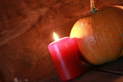Pumpkin and candle on old wooden Stock Photography