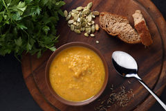 Pumpkin, carrot and lentil soup, bread and green on the wooden board Royalty Free Stock Photo