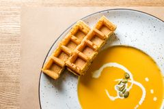 Pumpkin and carrot soup with cream and Belgian waffles on rustic wooden background. Flat lay with empty space stock photography