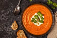 Pumpkin and carrot soup with cream, seeds and parsley. stock photos