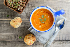 Pumpkin and carrot soup with nuts and bread buns on rustic wooden background Royalty Free Stock Photography