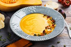 Pumpkin and carrot soup served with pumpkin seeds, potato chips stock photos