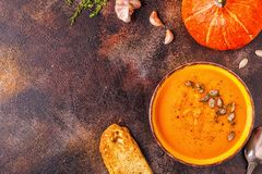 Pumpkin and carrot soup served with seeds stock image