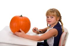 Pumpkin Carving. Young girl drawing on pumpkin for carving Stock Photo