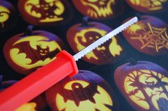 Pumpkin Carving Knife. A pumpkin carving knife with pumpkin carvings in background stock photo
