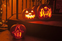 Pumpkin carvings. 3 carved pumpkins sit on the steps of a home on the night of halloween Stock Photos