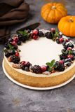 Pumpkin cheesecake with sour cream topping. And fresh seasonal berries and nuts Stock Photos