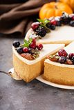 Pumpkin cheesecake with sour cream topping. And fresh seasonal berries and nuts with a slice taken out Stock Image