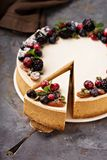 Pumpkin cheesecake with sour cream topping. And fresh seasonal berries and nuts with a slice taken out Royalty Free Stock Photo