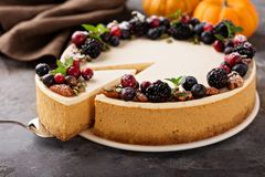 Pumpkin cheesecake with sour cream topping. And fresh seasonal berries and nuts with a slice taken out Royalty Free Stock Photos