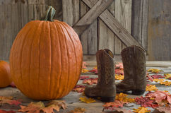 Pumpkin and a child's cowboy boots with Fall leaves on country porch Royalty Free Stock Image