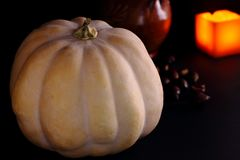 Pumpkin. Chestnuts and candle in background. Dark background royalty free stock photos