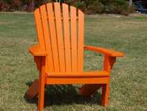 A Pumpkin Colored Slot Back Adirondack Chair Stock Images