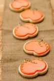 Pumpkin cookies. Orange pumpkin-shaped sugar cookie cut-outs lay in a line on a piece of burlap Royalty Free Stock Photos
