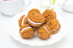 Pumpkin cookies with cream filling on a white plate Stock Photos