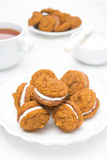 Pumpkin cookies with cream filling on a white plate and tea Stock Image
