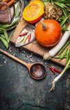 Pumpkin , cooking spoon and vegetables ingredients on dark rustic background, top view Stock Photo