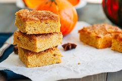 Pumpkin cornmeal bars with spices on a wooden background. Close royalty free stock photo