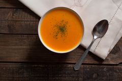 Pumpkin cream with chives and parsley on wooden table stock photo