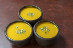 Pumpkin cream-soup with addition of pumpkin seeds and spices, view from above, studio shot. Clay plate of pumpkin cream-soup with. Addition of pumpkin seeds and royalty free stock photography