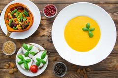 Pumpkin cream soup with basil leaves, baked pumpkin with vegetables: carrots, beans, haricot, bruschettas with cream cheese and t stock image