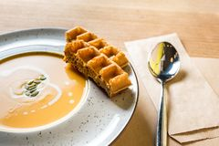 Pumpkin cream soup with Belgian waffles in white bowl. Traditional autumn food. Photo from home kitchen or family cafe. Pumpkin cream soup with Belgian waffles royalty free stock photos