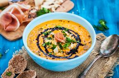 Pumpkin cream soup bowl, served with sesame, prosciutto, parmesan cheese, olive oil, balsamic royalty free stock photos