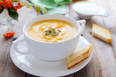Pumpkin  cream soup and bread on wooden table Royalty Free Stock Images