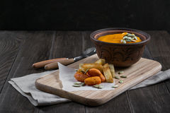 Pumpkin cream soup in a clay bowl with snack fried croutons bread,baked carrots. Stock Images