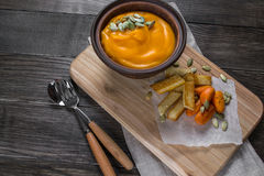 Pumpkin cream soup in a clay bowl with snack fried croutons bread,baked carrots. Royalty Free Stock Photos