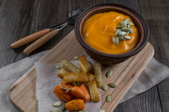 Pumpkin cream soup in a clay bowl with snack fried croutons bread,baked carrots. Royalty Free Stock Photography