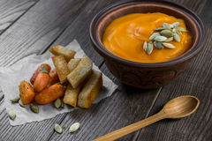 Pumpkin cream soup in a clay bowl with snack fried croutons bread,baked carrots Royalty Free Stock Photos