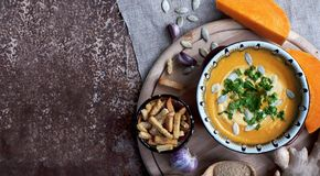 Pumpkin soup with ginger and crackers on grange background Royalty Free Stock Images