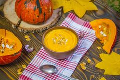 Pumpkin cream soup with cream and pumpkin seeds on wooden background selective focus Royalty Free Stock Photography