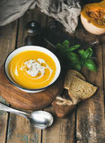 Pumpkin cream soup with fresh basil, spices and grilled bread Royalty Free Stock Images
