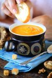 Pumpkin cream soup with a hand holding piece of bread Royalty Free Stock Photos