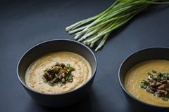 Pumpkin cream soup with herbs and nuts, served in a dark bowl. Proper and healthy food. Vegetarian dish. Dark background stock images