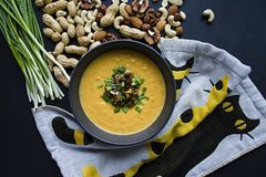 Pumpkin cream soup with herbs and nuts, served in a dark bowl. Proper and healthy food. Vegetarian dish. Dark background stock image