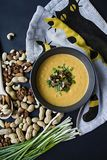 Pumpkin cream soup with herbs and nuts, served in a dark bowl. Proper and healthy food. Vegetarian dish. Dark background royalty free stock photo