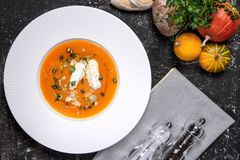 Pumpkin cream soup with homemade cheese and herbs stock photo