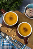 Pumpkin cream soup in mugs on gray blue background stock image
