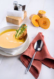 Pumpkin cream soup with parmesan toast in a white plate. Pumpkin pieces on a white table. Lunch at the restaurant Royalty Free Stock Photo