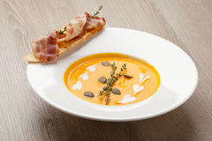 Pumpkin cream soup purée with bread slice, bacon and seeds Royalty Free Stock Photography